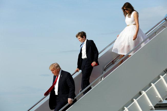 川普夫婦和兒子巴倫16日搭乘「空軍一號」返回華府,川普下機時一馬當先,把梅蘭妮亞甩在後面。(路透)