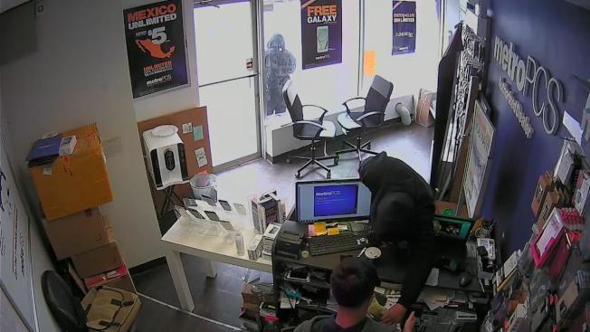 搶匪把手伸到收銀機裡拿錢。(視頻截圖)