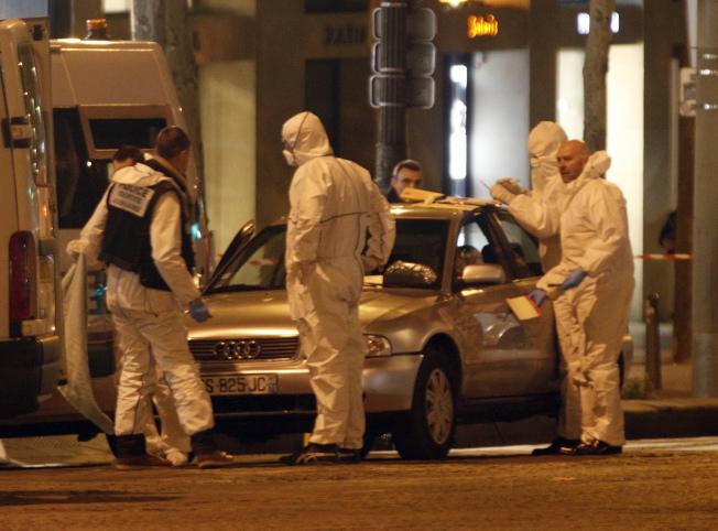 巴黎恐襲的一名槍手喪生,鑑識人員在他的汽車上蒐證。(美聯社)