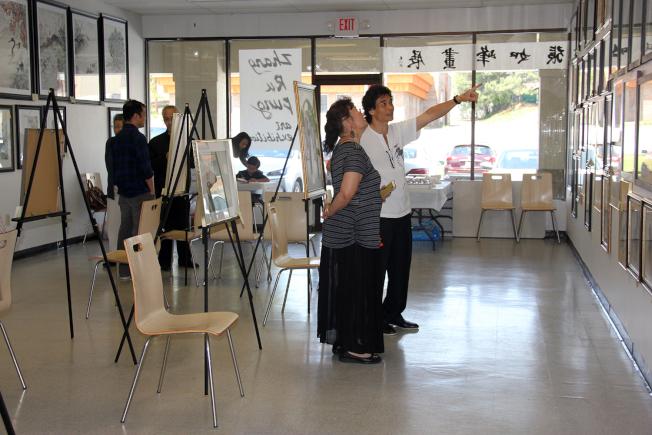 張如峰(右)向參觀者介紹他的畫作。(章慧娟/攝影)