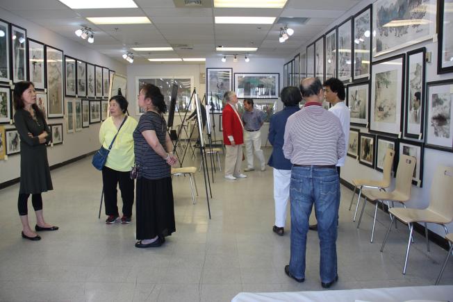 畫展現場,左為亞城美術協會會長陳光玉。(章慧娟/攝影)