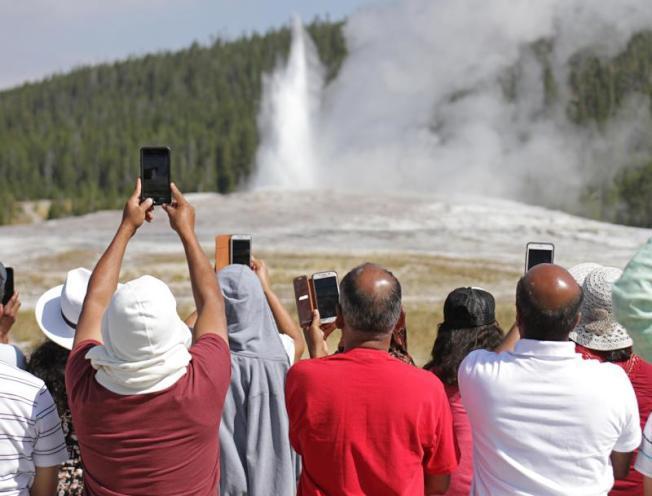 遊客圍觀黃石公園著名的「老忠實」噴泉。(黃石國家公園提供)