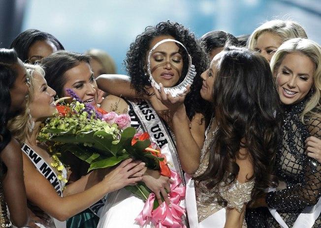 麥庫洛在其他選美會佳麗包圍下,檢視她贏得的美國小姐后冠。(美聯社)