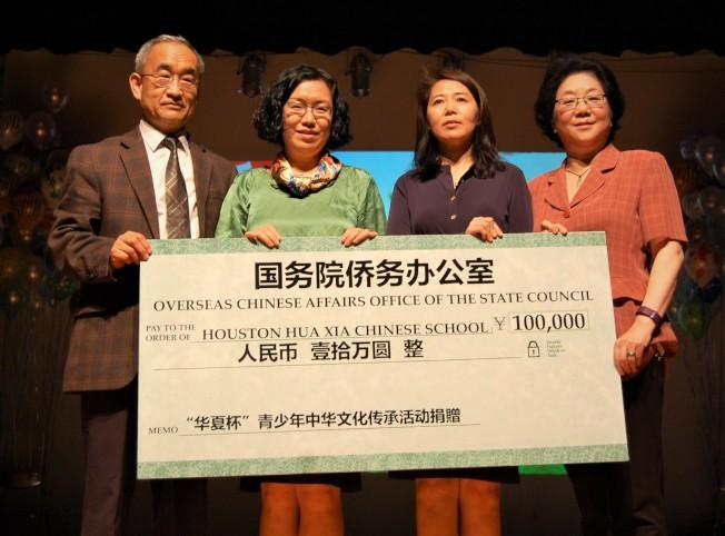中國駐休士頓副總領事劉紅梅(左二)代表國僑辦向華夏中文學校贈送捐款支票10萬元人民幣,華夏中文學校副理事長張憲寬(左一)、總校長薩茹(右二)、副理事長唐藝傑(右一)接受捐款。(記者賈忠/攝影)