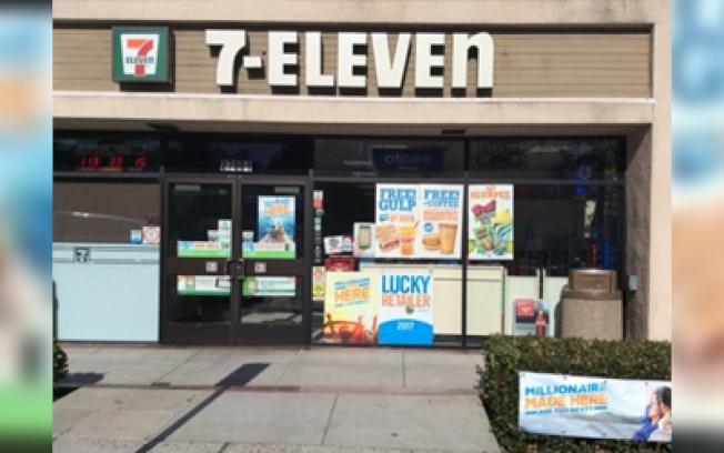 押中6100萬元兆彩頭獎的拉古納岡7-Eleven便利商店,店門旁邊玻璃窗貼出「幸運投注站」海報,矮樹叢亦掛出「百萬富翁在此誕生」布條。(加州彩券局提供)