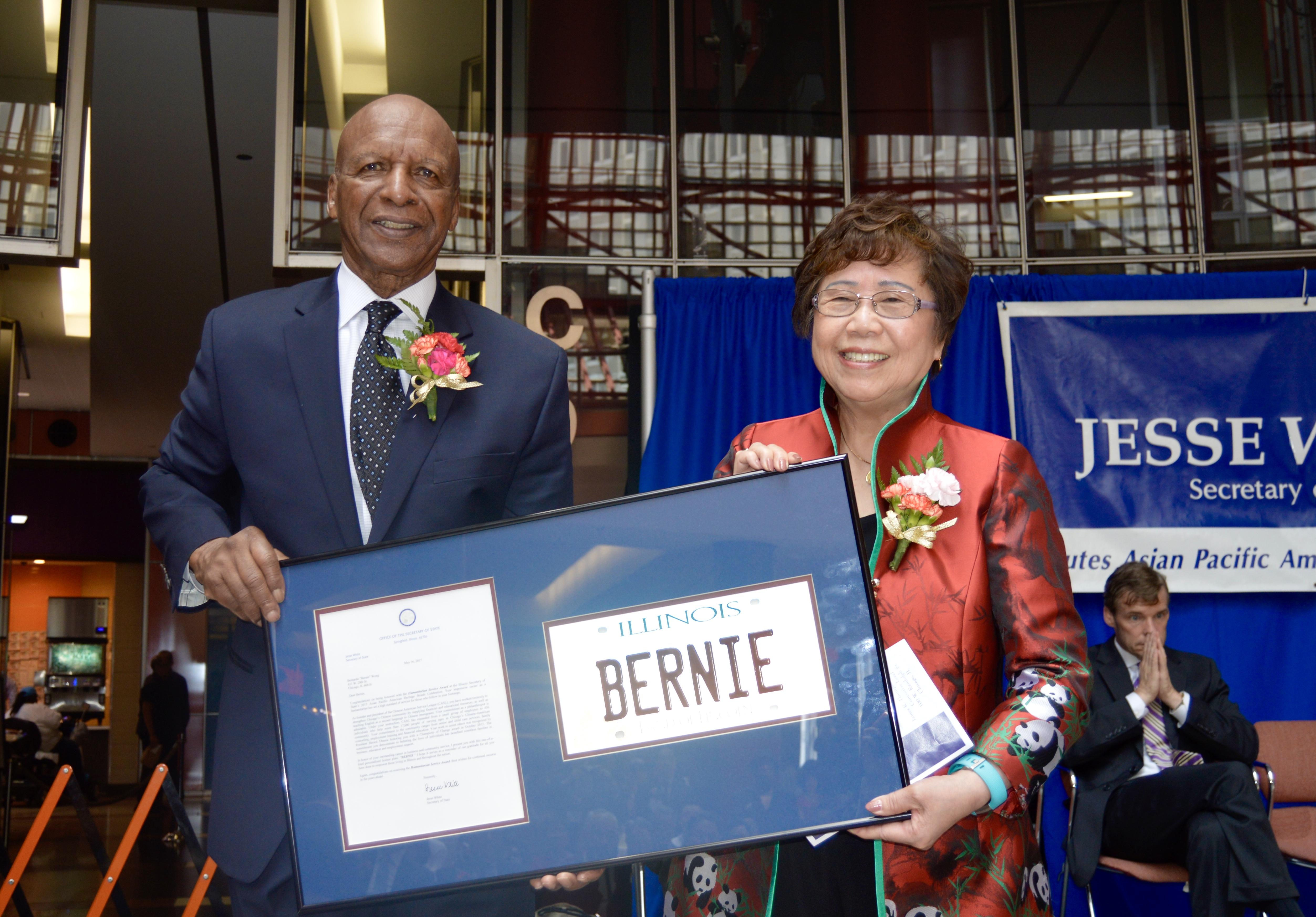 芝加哥華諮處創始人之一的黃羅瑞雄(右),16日在伊利諾州州務卿懷特(左)在州府大樓大廳舉行的亞太裔傳統月慶祝活動中,獲頒「人道服務獎品」。(記者董宇/攝影)