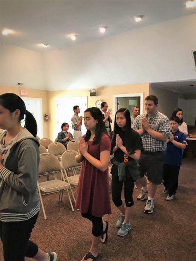 青少年和孩童跟著大人恭敬合十繞室。(記者王明心/攝影)