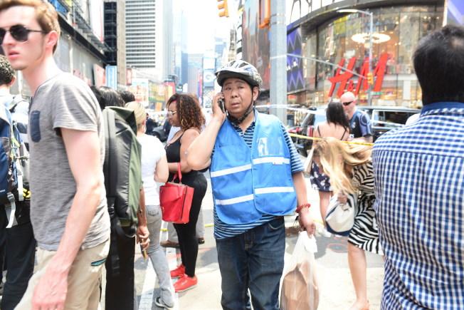 紐約時報廣場18日中午發生嚴重車禍,警方封守廣場四周道路進行調查,餐館送外賣的員工被阻攔在外圍。(記者許振輝/攝影)