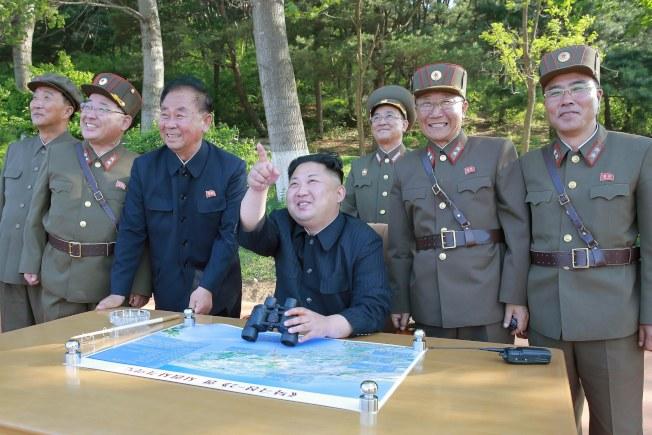 北韓官方朝中社發布的照片顯示,北韓領導人金正恩(中坐者)現場視察中程彈道導彈試射。(歐新社)