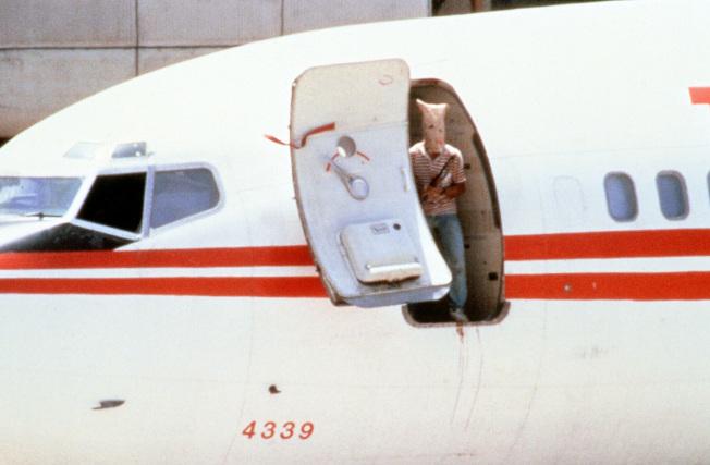 6月29日,一名蒙面恐怖份子走出機艙外,與地勤人員交談。(Getty Images)