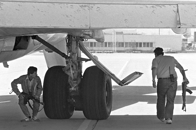 6月19日,恐怖份子在飛機下方戒備。(Getty Images)