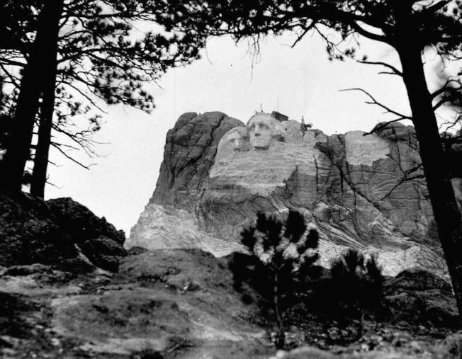 1933年5月2日,華盛頓像雕刻工程。原計畫傑佛遜像(左,已見雛形)是在華盛頓像右側,因沒有足夠面積的岩石,而改在華盛頓像右側。(美聯社)