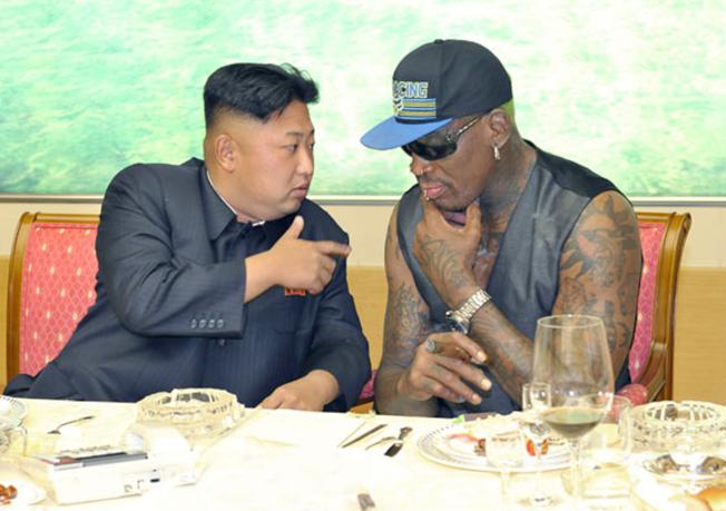 2013年9月北韓勞動新聞在首頁刊出北韓領導人金正恩(左)與羅德曼在晚宴上交談。(美聯社)