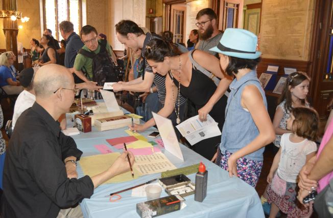 書法愛好者湯偉和猶太裔書法家Zelig Mandel為民眾題字。(記者俞姝含/攝影)
