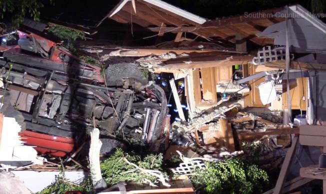 一輛道奇卡車離奇飛墜橙縣約巴林達市一戶民宅的屋頂,造成車上兩人死亡,屋內五人受傷。(KTLA)