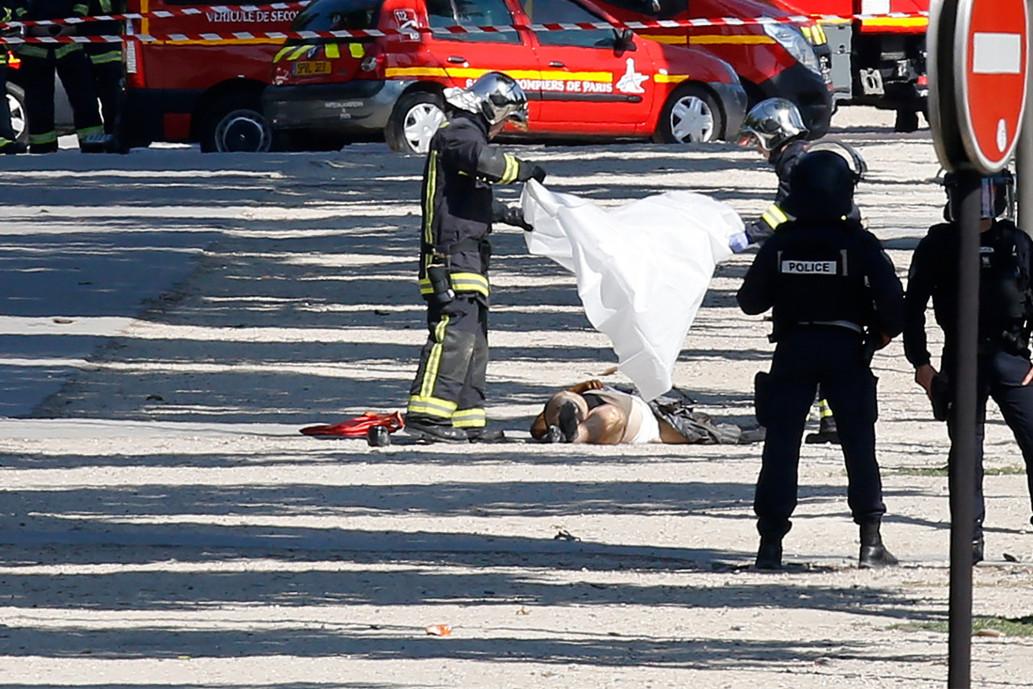 巴黎警方將白布幅罩在炸彈客屍體上。(路透)