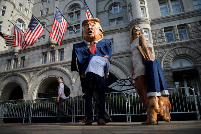川普總統28日晚在華府川普大酒店舉行首次連任募款餐會,民眾在酒店前抗議健保法案。(路透)