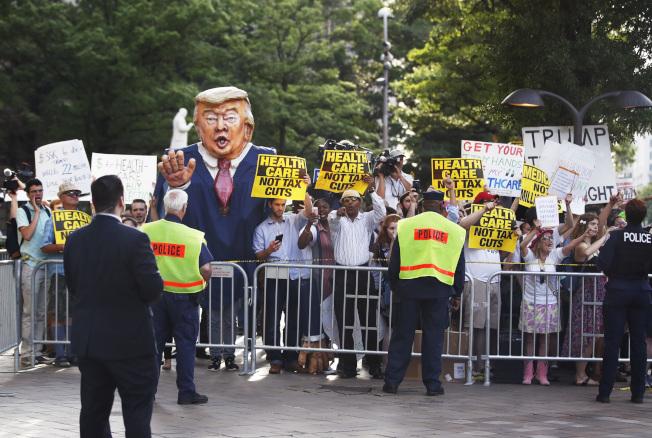 川普總統28日晚在華府川普大酒店舉行首次連任募款餐會,大批民眾在酒店前抗議健保法案。 (美聯社)