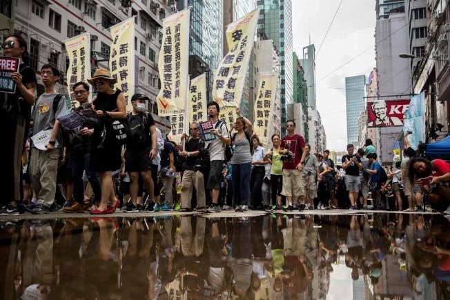港數以萬計爭取民主的抗議人士,1日頂著盛夏雨勢走上街頭,舉著「民主」、「釋放劉曉波」等標語,從維多利亞公園遊行前往金鐘政府總部。 (Getty Images)