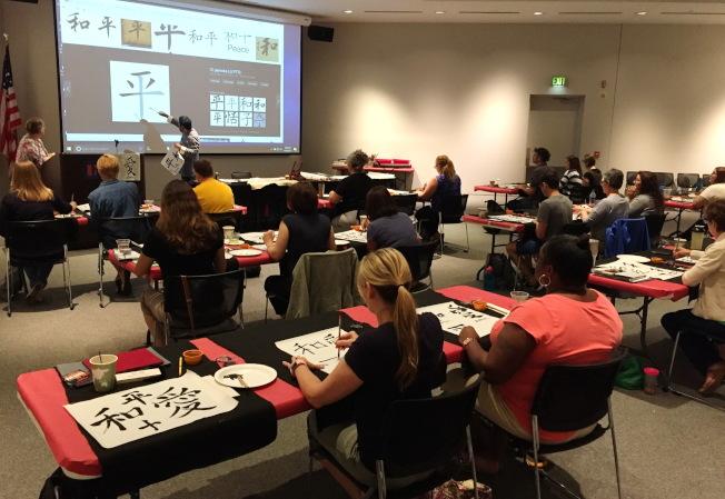 中國文化藝術培訓班學員們上書法課,學習用毛筆寫書法。 (南佛大孔子學院提供)