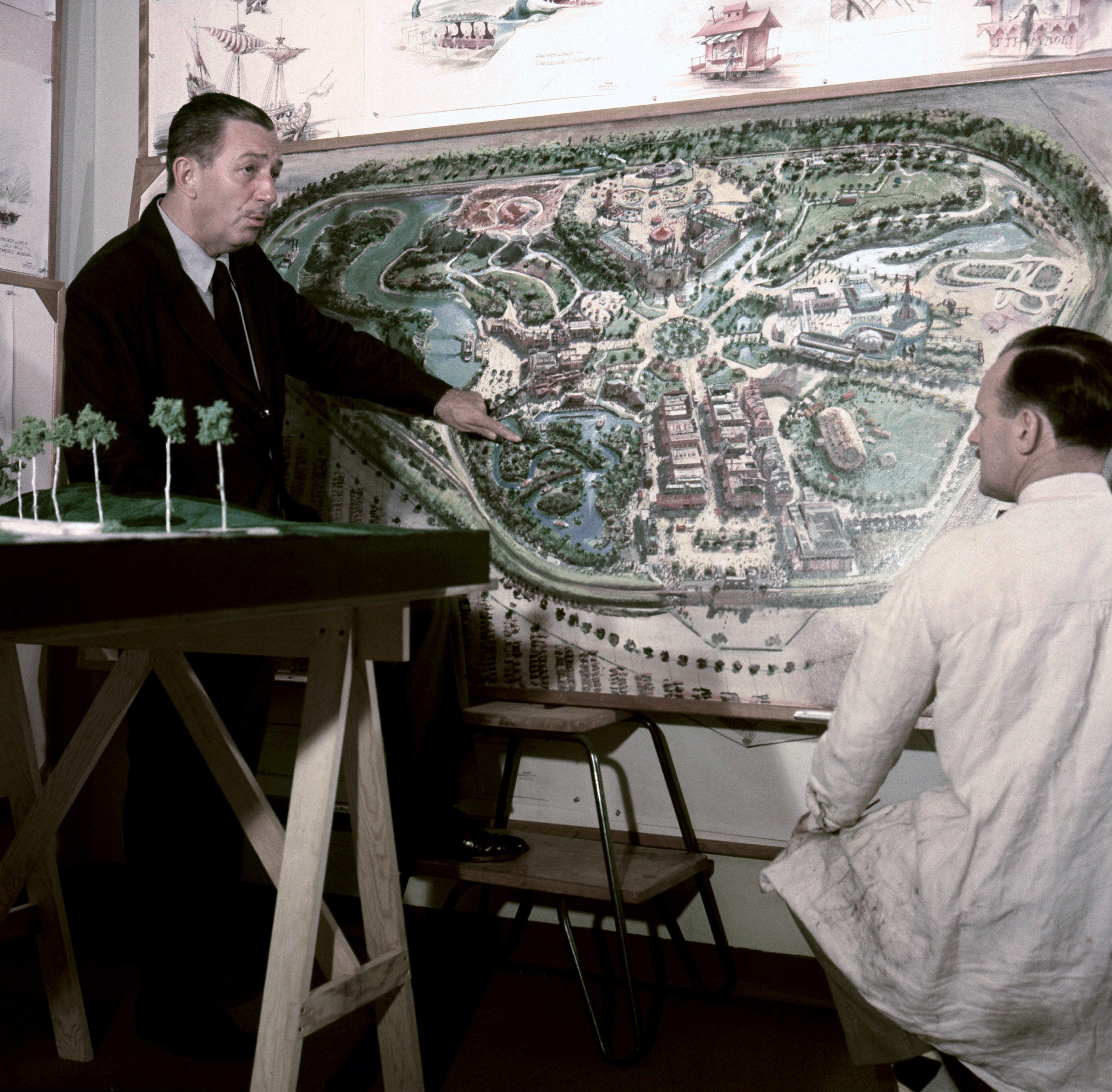 1954年華特‧迪士尼(左)站在加州迪士尼的規畫圖前跟工作人員聊天。(Getty Images)