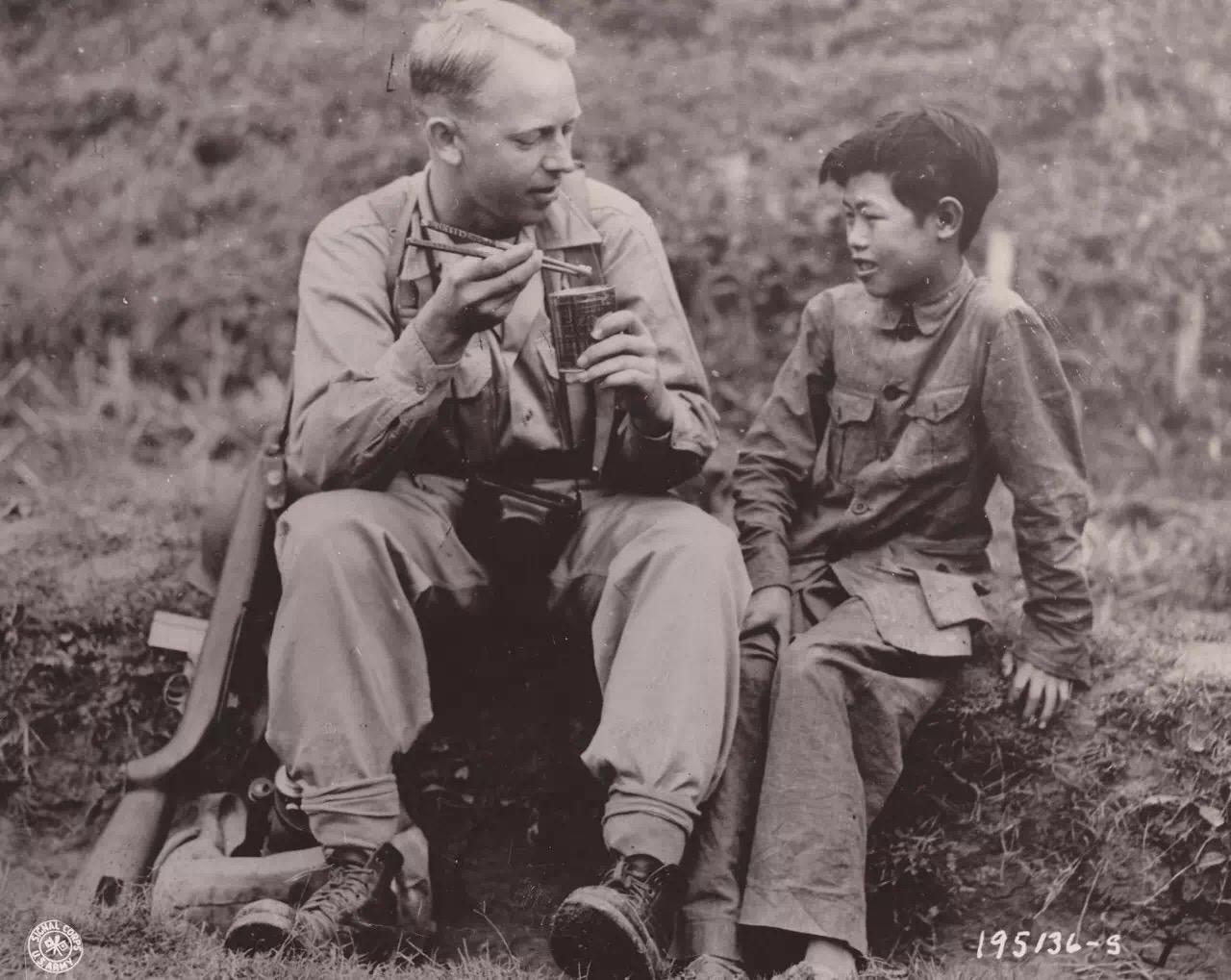 在中緬印戰場,來自北達科塔州的通信兵攝影師上等兵亞瑟‧海吉用筷子吃美國野戰口糧,身旁的小孩李田(右,音譯)在教他使用筷子。1944年5月6日攝於中國。(中國深圳市越眾歷史影像館)
