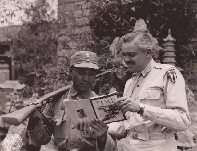 1945年6月29日,來自愛荷華州達文波特的韋恩‧蒂森中校,正在向一名中國警衛展示《時代週刊》。1945年6月29日攝於中國昆明。(中國深圳市越眾歷史影像館)