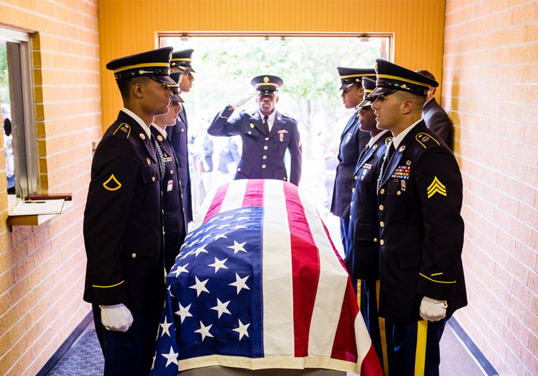 奧斯福德回家了!他的棺木覆上美國國旗,由美國現役軍人抬棺。(王本桓提供)