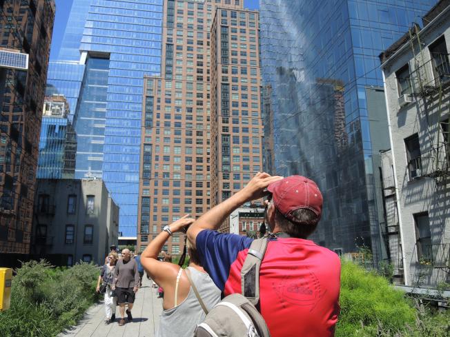 高線旁拔地而起的豪華大樓,成為民眾爭相拍照的對象。(記者俞姝含/攝影)