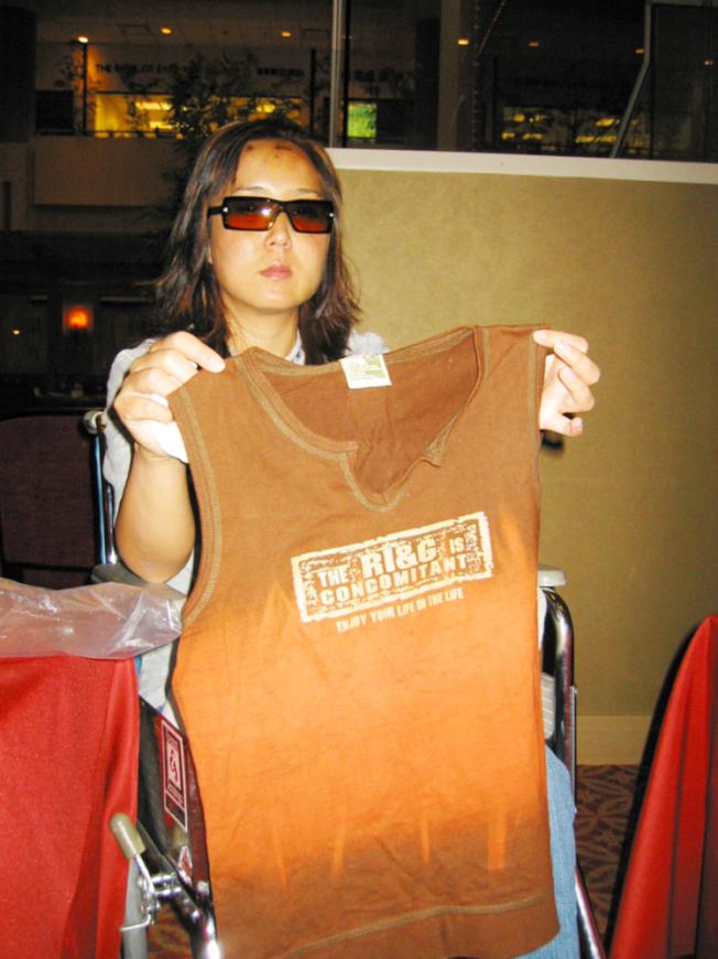 趙燕拿著自己出事時身穿的T恤。(本報資料照片)