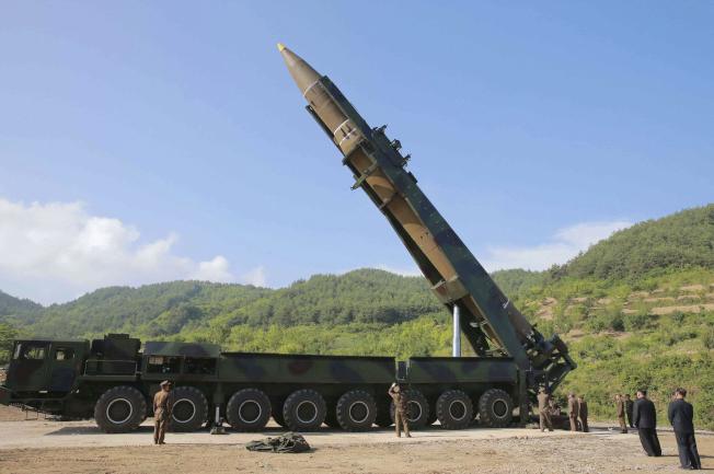 北韓官方朝中社發布的照片顯示,北韓領導人金正恩(右下方)正視察火星-14型洲際彈道飛彈。(美聯社)