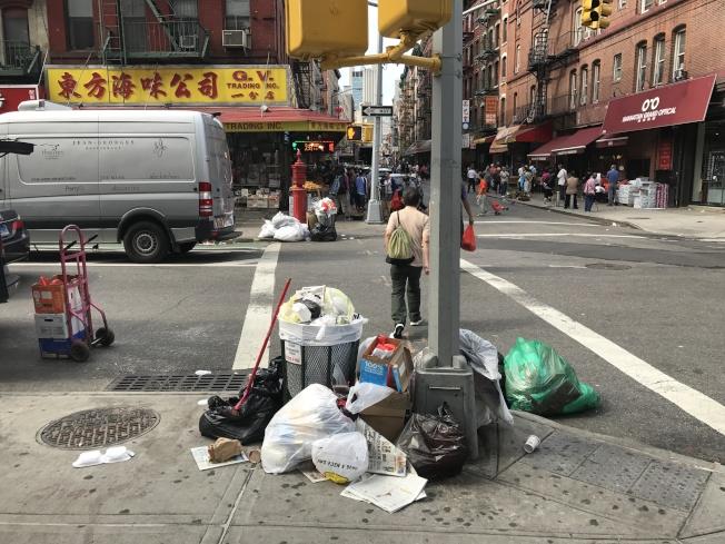 店門前的垃圾桶經常爆滿,私人清潔公司工作人員經常不準時收垃圾,店員只能自己清理。(張明鳳提供)