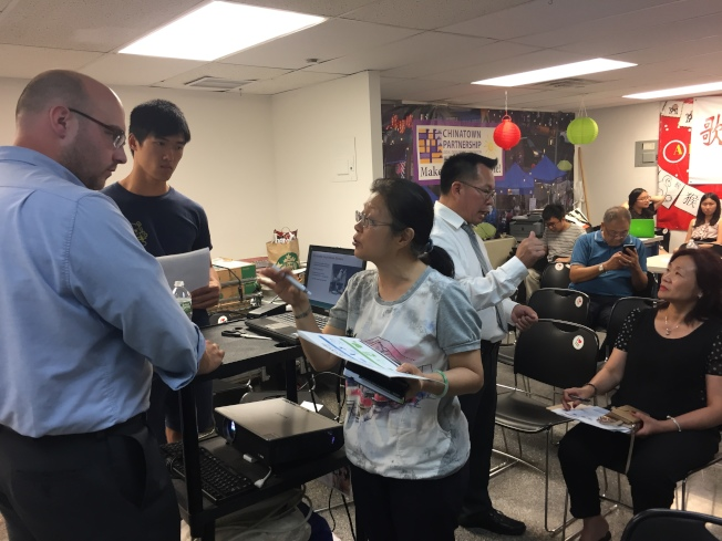 華裔商家向市清潔局工作人員提問。(記者俞姝含/攝影)