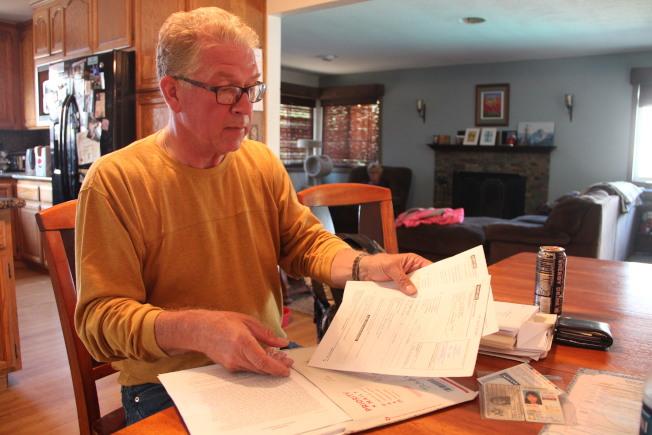 戴納德展示自己為女兒申請綠卡和國籍的種種文書資料。(記者李晗/攝影)