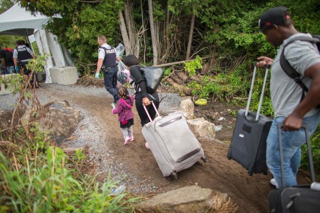 加拿大皇家騎警引導越界的無證移民,辦理登記。(Getty images)