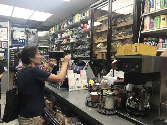 法拉盛緬街7號線地鐵站出口的一家雜貨鋪中12日至少千餘人購買勁球獎券。(記者牟蘭/攝影)
