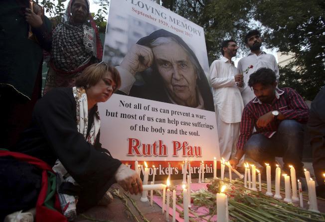 巴基斯坦民眾點蠟燭向普福修女致敬。(美聯社)