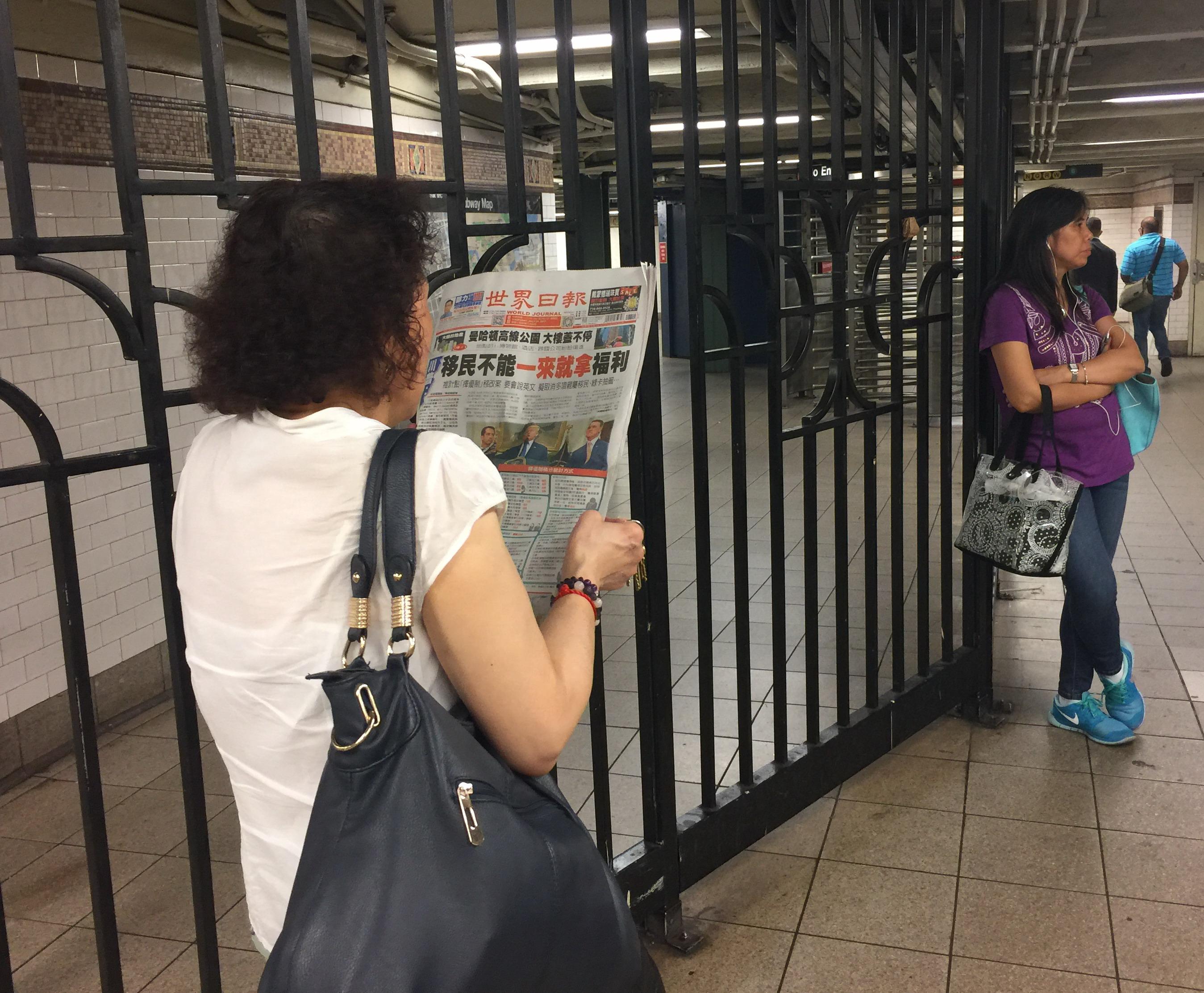 紐約民眾在地鐵站台上閱讀世報福利系列報導。(記者顏嘉瑩/攝影)