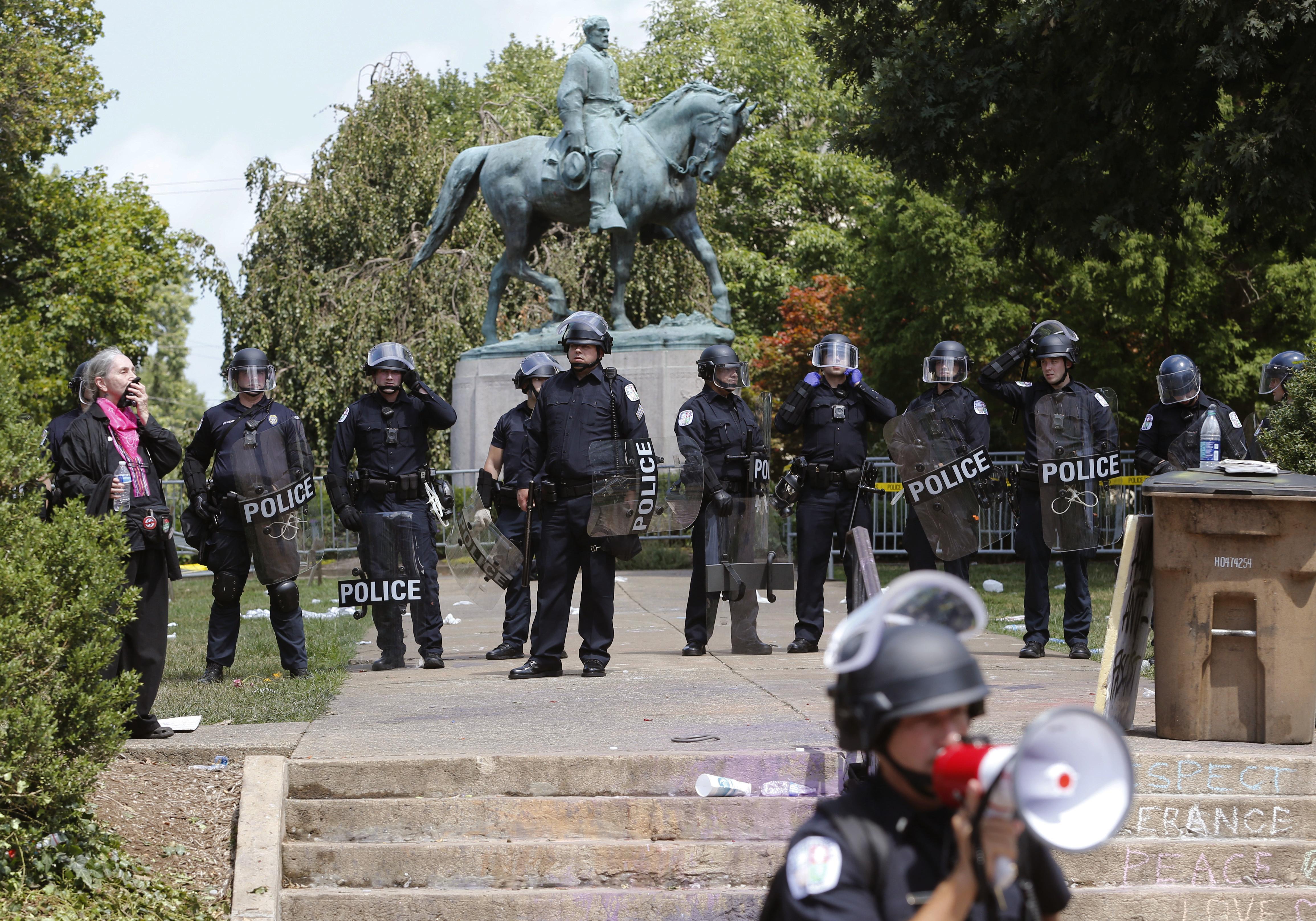 維州警方12日圍繞在夏洛茲維爾市 (Charlottesville) 的白人主義象徵李將軍 (Gen. Robert E. Lee) 雕像前。上百名白人至上主義擁護者12日在此進行大規模示威。(美聯社)