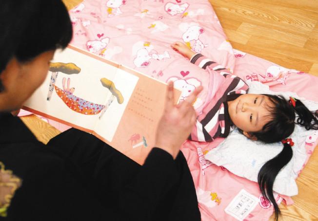 睡前用英語說床邊故事,也可訓練孩子聽力。(本報資料照片)