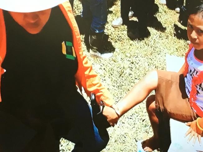 幫幫忙基金會志工幫忙瓜地馬拉當地小孩穿鞋。(幫幫忙基金會提供)