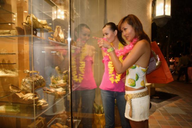 7月夏威夷觀光客消費金額較去年同期成長了近10%。圖為兩名日本遊客在威基基逛街購物。(Getty Images)