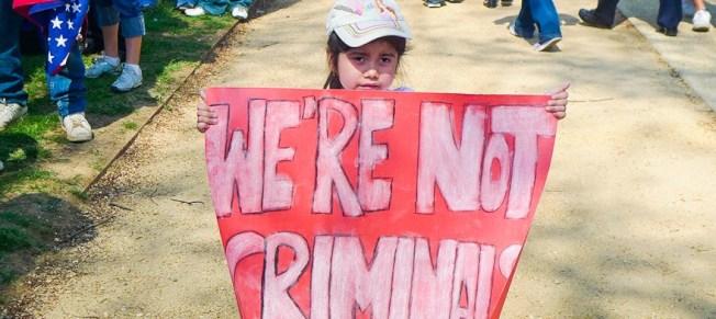 亞裔小夢想家舉牌「我們不是罪犯」,抗議川普政府要廢除DACA。(夢想家中心提供)