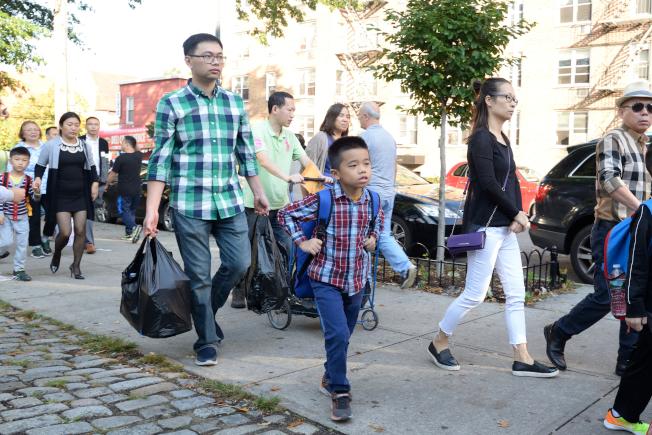 華裔家長當起「挑夫」,拎著大包小包文具帶孩子上學。(記者朱澤人/攝影)