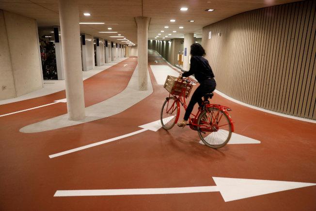 一名自行車騎士在停車場通道移動。(路透)