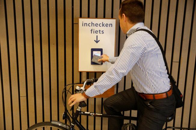 自行車騎士掃描卡片,進入停車場。(路透)
