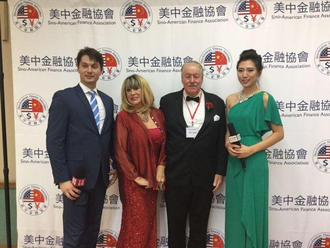 志強(左)與華人女主持搭檔主持經濟論壇。(Victor Migalchan提供)