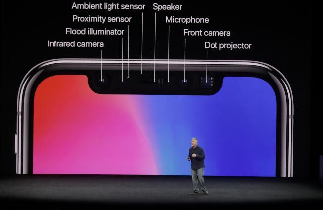 蘋果全球市場副總裁席勒介紹iPhone X的多重功能。左方上起為紅外線鏡頭、泛光燈、趨近傳感器、光度感應器,右方上起為揚聲器(喇叭)、麥克風、前置鏡頭、投影器。(美聯社)