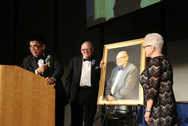 華人醫務中心45周年慶,晚宴上為衛優俊(中)準備了他的肖像油畫。(記者俞國梁/攝影)