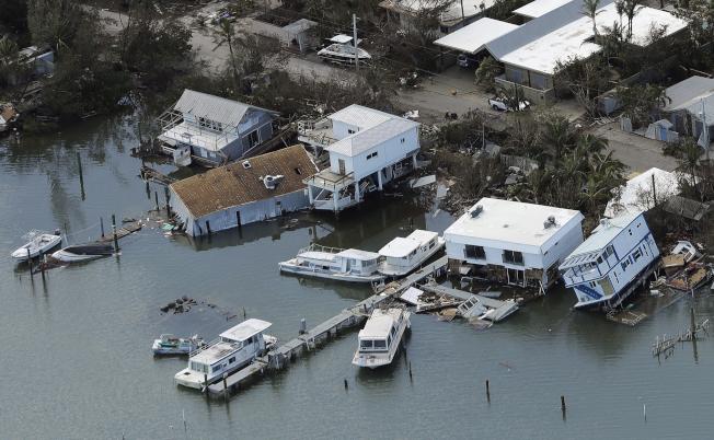 佛州西礁島(Key West)在厄瑪颶風侵襲下受災慘重,圖為被風吹到水裡的民宅。(美聯社)